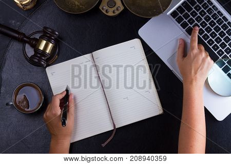 Workspace hero header with law gavel, legal book and laptop keyboard, hands typing and writting in notebook, top view flatlay scene