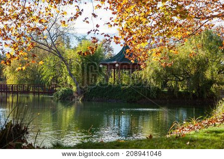 A large pond with surrounding gardens gazebo and a bridge lit by afternoon sunshine in the fall season.