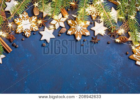 Christmas background with cookies fir branches lights and spices on dark blue.