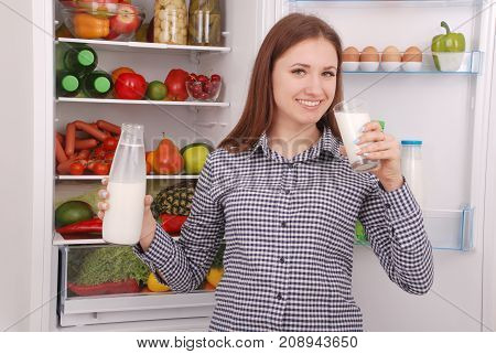 Young girl hold bottle of milk standing near the open fridge in the kitchen