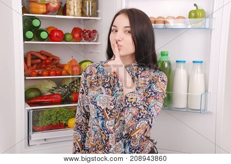 Young girl holding her finger over her mouth don't talk. Secret woman. On the refrigerator background