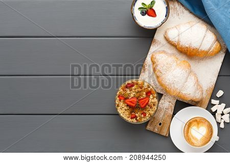 Traditional french breakfast menu background. Yogurt with fresh berries, cup of coffee, muesli and croissants on grey wooden table, top view, copy space