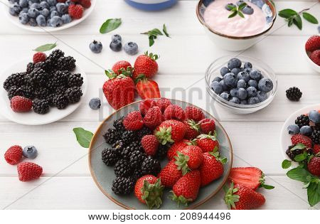 Healthy breakfast background. Light greek yogurt, fresh strawberries, raspberries, blueberries and blackberries. Low fat morning meals and healthy start of the day. Detox and eating right concept