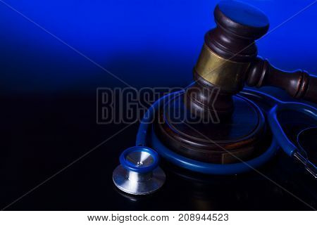 Wooden law gavel with stethoscope - medical law and justice concept