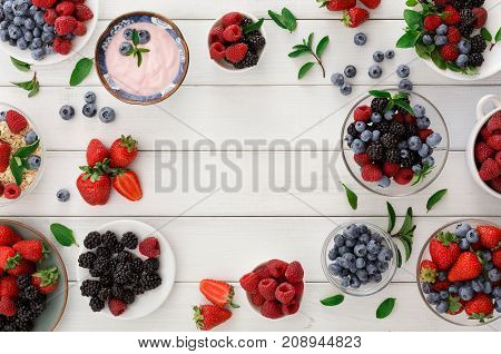 Healthy breakfast background. Light greek yogurt, fresh strawberries, raspberries, blueberries and blackberries frame on white wood with copy space. Detox and eating right concept, top view