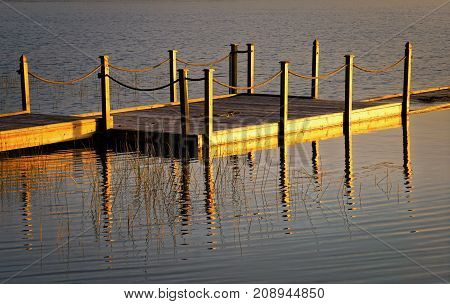 Floating dock reflected in calm lake waters at evening light
