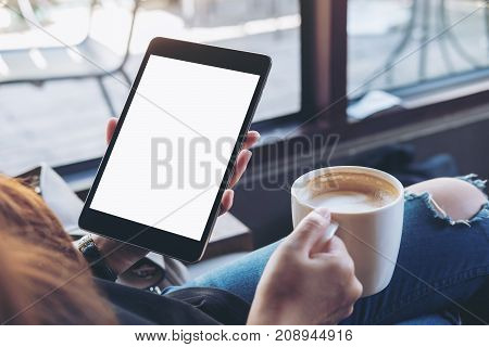 Mockup image of woman's hands holding black tablet pc with white blank screen and coffee cup of hot latte sitting in modern cafe