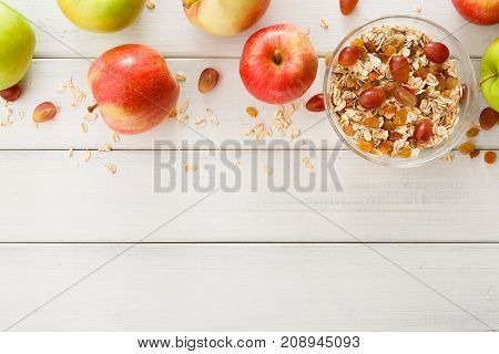 Healthy breakfast background. Oat flakes with raisins and lots of ripe apples on white wooden table with copy space. Diet morning meals with seasonal fruits and cereals, top view