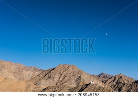 Landscape mountain image with the moon in clear blue sky background