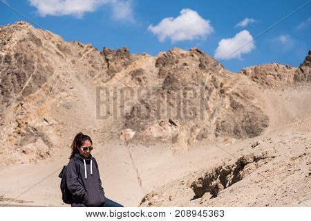 Portrait image of a beautiful Asian woman tourist standing in front of mountain and blue sky background