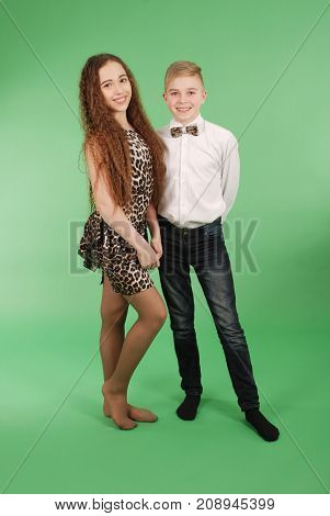 Couple of teens standing isolated on a green background