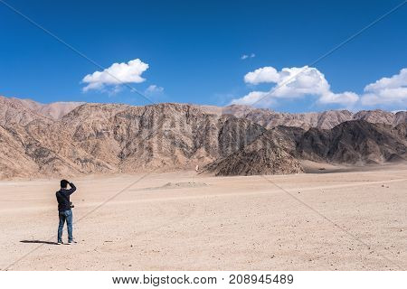 A man photographer taking a landscape photo of mountains and blue sky in Ladakh India