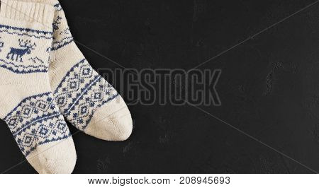 Pair of wool socks with pattern deer on black background. Warm winter stockings with traditional christmas ornament, copy space