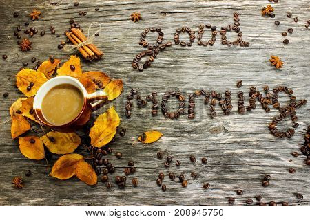 Good morning from coffee beans. A cup of coffee on a wooden background strewn with autumn yellow leaves and anise. Greeting for breakfast. View from above