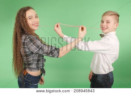 Young boy and girl stretching from chewing gum which he carries in his mouth isolated on green background