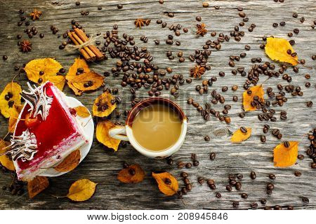 a cup of coffee and a cake on a wooden table strewn with coffee beans autumn yellow leaves and anise. View from above.