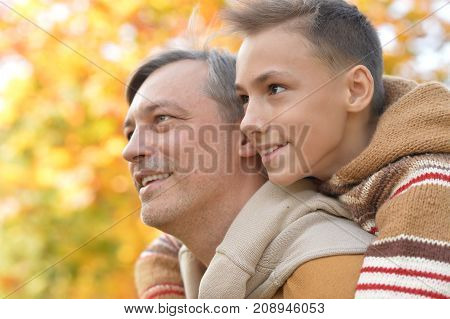 Portrait of father and son in autumn park