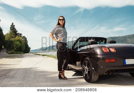 Fashionable young woman stands near the cabriolet car