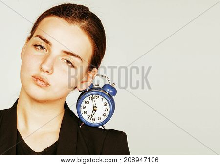 young beauty woman in business style costume waking up for work early morning on white background with clock