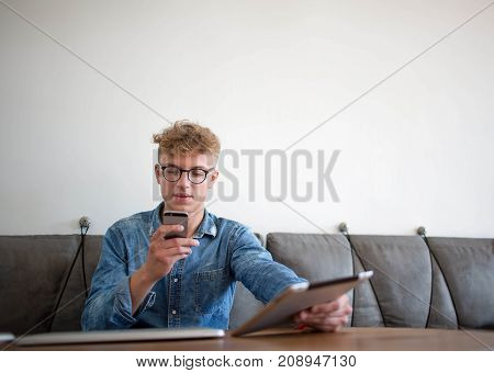 Man successful business coach reading news in internet via mobile phone, waiting for video call on touch pad. Young male student chatting on cell telephone, sitting with digital tablet in coffee shop