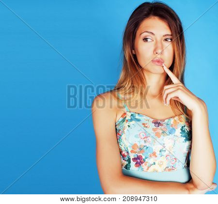 young pretty woman fooling around on blue background close up smiling