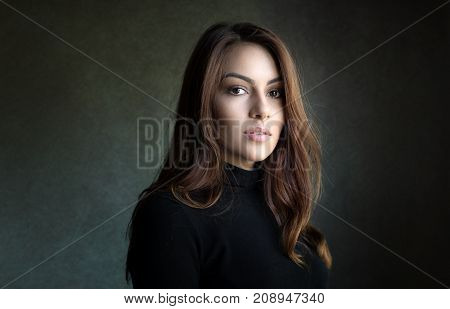 Portrait of a beautiful woman. Indoor with natural light coming from a window