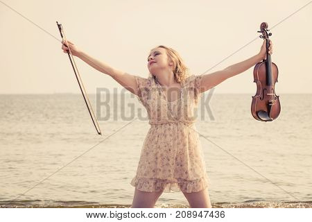 Music love everyday passion concept. Woman on beach near sea holding violin enjoying her hobby