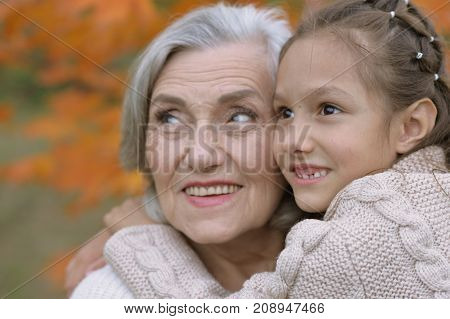 Portrait of grandmother and granddaughter hugging  outdoors