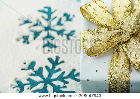 Elegant Gift Box Wrapped in Grey Silver Paper with Polka Dots Golden Ribbon on Snowy Background with Blue Snow Flakes. Christmas New Years Presents Shopping Sale Advertisement. Copy Space