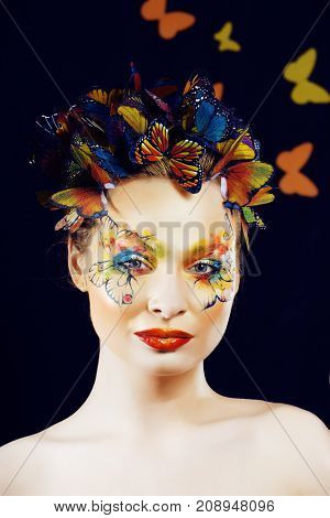 woman with summer creative make up like fairy butterfly closeup bright colored background