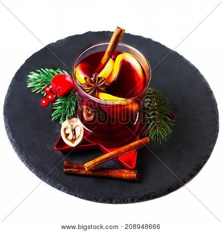 Christmas Hot mulled wine for winter with spices isolated on white background traditional drink on winter holidays closeup. Mulled wine or gluhwein composition on black slate board with Christmas Decorations