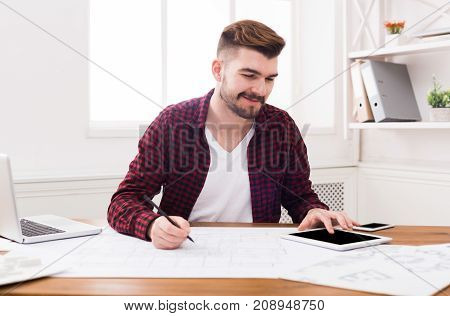Architect working on blueprint in office. Designer drawing building plan, copy space