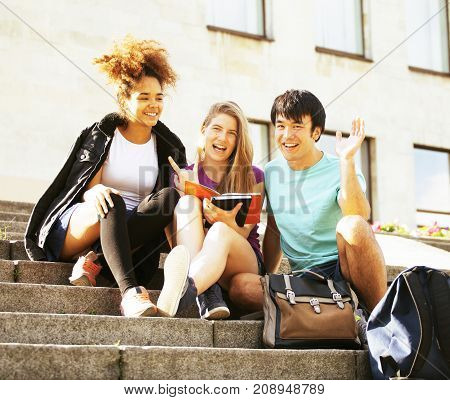 cute group of teenages at the building university with books huggings, smiling, back to school