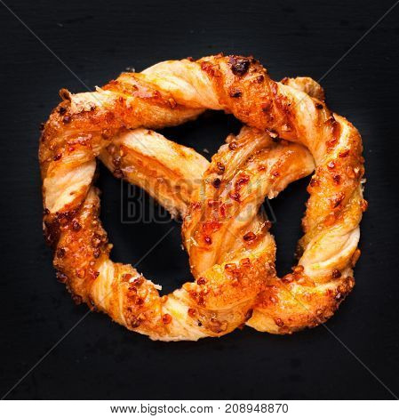 Delicious Fresh pastry on dark background. Sweet pretzels with powdered sugar. Closeup of beautiful delicious puff pastry