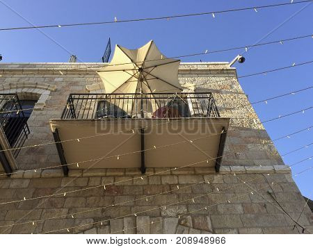 A balcony from below with parasols a historic street in the old town of Jerusalem. On the streets are lights chain tension.On the corner of a house is a surveillance camera to see