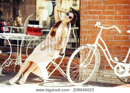 young pretty brunette woman after shopping sitting at cafe outside on street smiling, wearing dress and sunglasses, summer time
