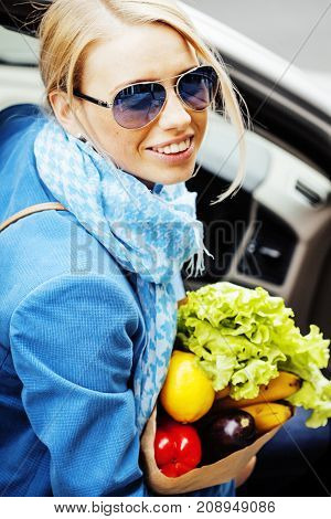 young pretty blond woman with food in bag walking on street healthy cheerful