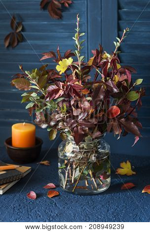Autumn still life - bouquet of autumn leaves candle notepad for drawing on the dark table. Autumn mood. Home interior
