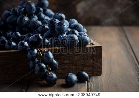 Fresh Black Grapes in Dark Wooden Tray on Wooden Table Selective focus