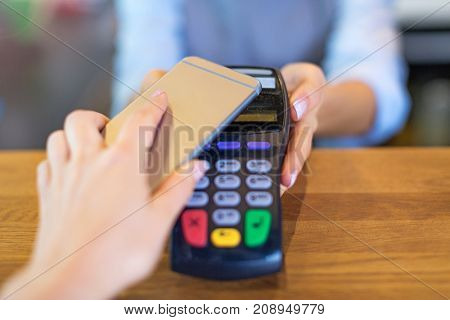 Customer Paying Through Mobile Phone In Cafe