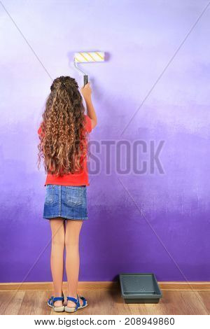 Little cute girl painting wall in room