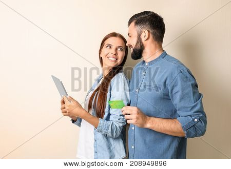 Young couple with tablet computer and credit card on color background. Internet shopping concept