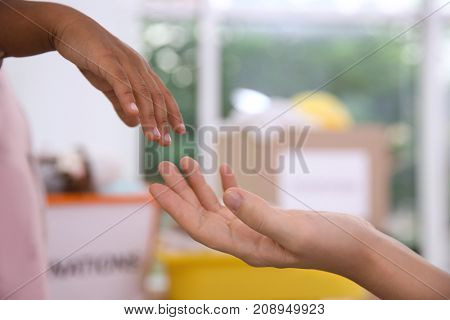 Little African-American child giving hand to woman on blurred background. Volunteering abroad concept