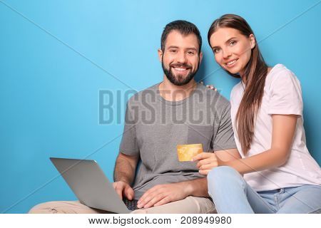 Young couple with laptop and credit card on color background. Internet shopping concept