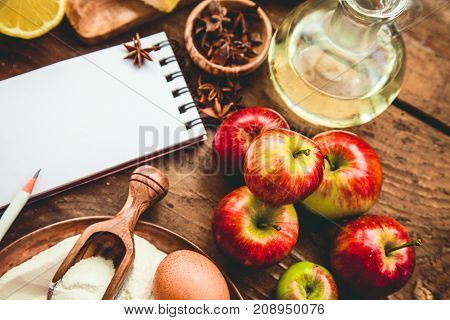 Baking background with paper for notes. Christmas and winter cookies ingredients.Baking pastry and cookies: apples spices sugar eggs on wood