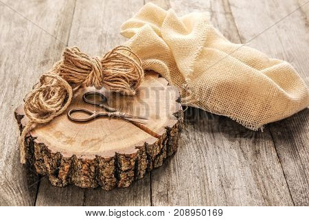 Composition with hemp cloth and twine on wooden background