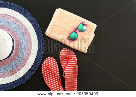 Composition with towel and summer accessories on dark background