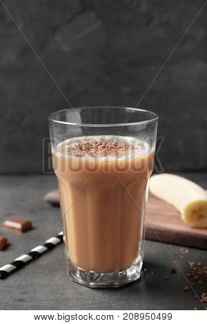 Glass with chocolate protein shake on table