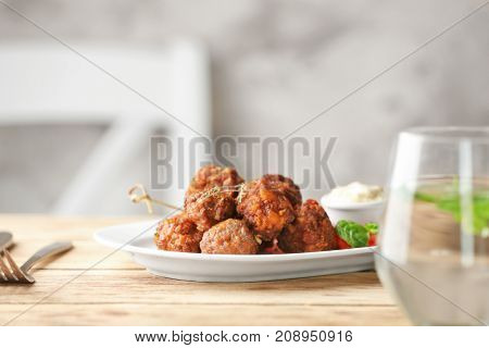 Plate with tasty sausage cheese balls on table