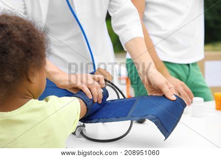 Volunteer doctor measuring blood pressure of poor African child outdoors, closeup